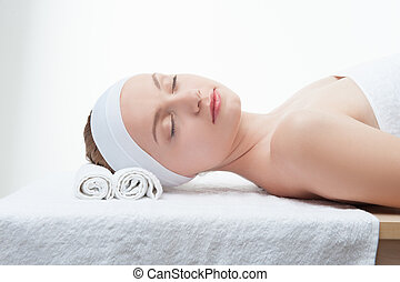 Young beautiful woman in spa relaxing on massage table