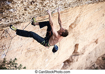 Rock climber on a face of a cliff - Rock climber on his...