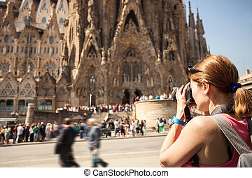 Young woman taking picture of Sagrada Familia. On April 16,...