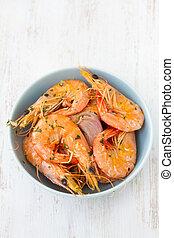 shrimps in blue bowl on white background