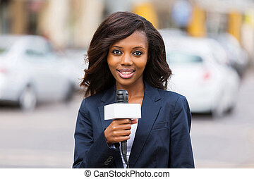 female african news reporter working outdoors - happy female...
