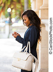 young african woman using smart phone - side view of young...