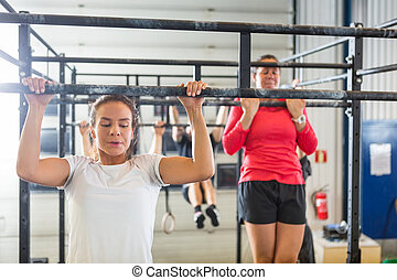 Athletes Doing Chin-Ups At Gym - Young female athletes doing...