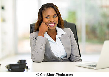 young african businesswoman sitting in office - portrait of...