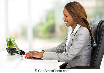 african office worker using laptop computer - attractive...