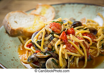 Homemade pasta with seafood and cherry tomatoes on wooden...