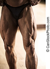 Bodybuilder showing his muscular thigh - Close-up of...
