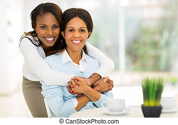 african daughter hugging middle aged mother