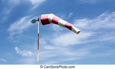 Red and white windsock blows agains - Wind sock - red and...