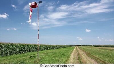 Red and white windsock blows agains - Off road has Wind sock...