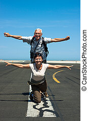 Happy couple imitating airplane at the airport - Happy...