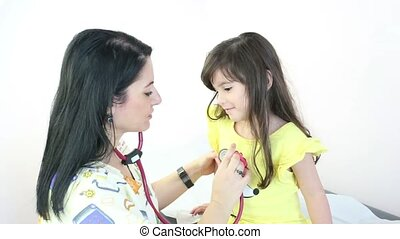 Doctor or nurse auscultating child
