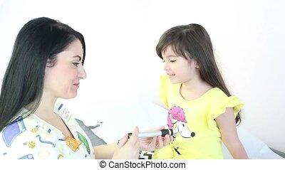 Female Pediatrician performing an eye exam on a female child...