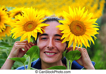 Beautiful woman in the middle of a sunflower field -...