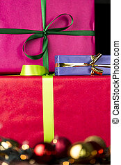 Three wrapped gifts, bowknots, spheres and glitters - The...