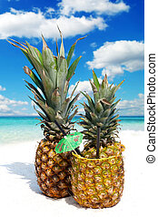 Fruity pineapple cocktail on the sandy beach with straw and...