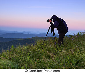 Photographer silhouette against the rising sun in the...