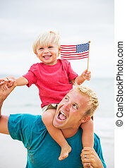 Father and son playing on the beach with American flag. USA...