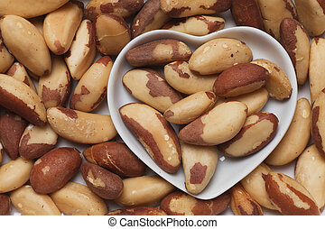 Brazil nut, healthy food ingredient in heart shaped tray