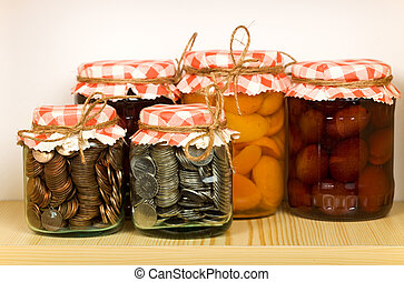 Savings concept with money canned in glass jars on the shelf