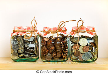Saving money concept with coins put away in glass jars on a...