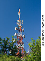Telecommunication tower between trees above the town The...