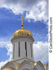 Dome of the orthodox temple against the sky with clouds