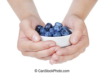female teen hands holding ripe blueberries in bowl, isolated...