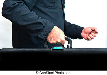 Hands of a man carry travel suitcase against white...