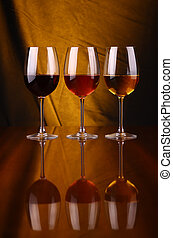 Wine glasses - Glasses of red, rose and white wine over a...