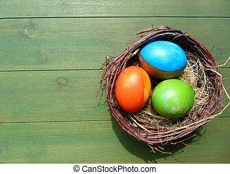 Easter eggs in bird nest - Colorful Easter eggs lying in...