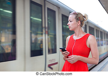 Young woman on platform of railway station. - Young woman in...