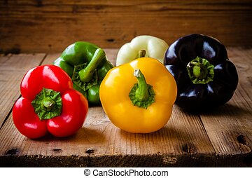 Red, green, black, white and yellow bell peppers on wooden...