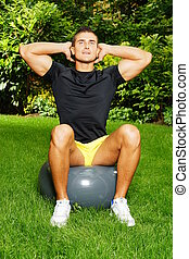 Young man exercises with fitness ba