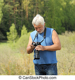 Old man with gray hair into the Wildlife. Old photographer...