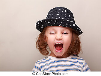Screaming kid girl in hat with open mouth on empty space...
