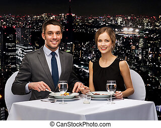 smiling couple eating main course at restaurant -...