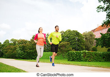 smiling couple running outdoors - fitness, sport, friendship...