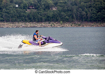 Riding a Jet ski. - Young man riding jet boat on a summer...