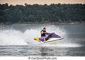 Riding a Jet ski - Young man riding jet boat on a summer day...