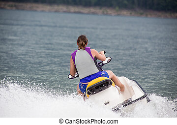 Yound Woman riding a jet ski - Young woman riding a jet boat...