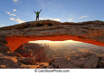 Silhouetted person standing on top of Mesa Arch, Canyonlands...