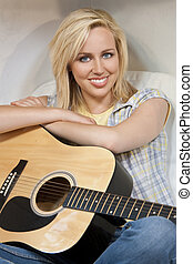 Beautiful Young Woman Playing A Guitar - A beautiful blond...