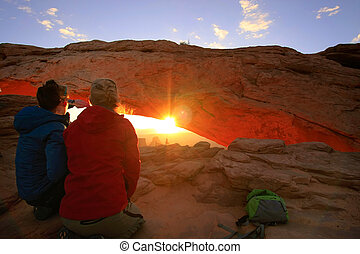 Tourists watching sunrise at Mesa Arch, Canyonlands National...