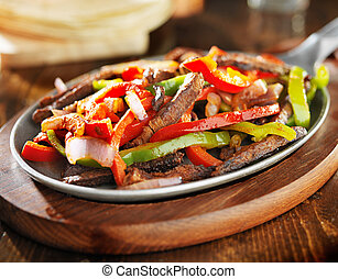 mexican beef fajitas in iron skillet with tortillas in...