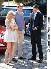 Salesman Showing Contract Paper To Couple By Car