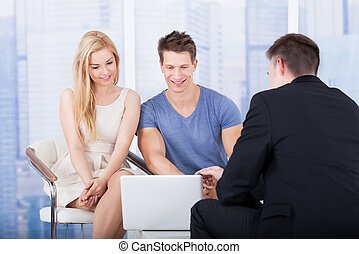 Financial Advisor Explaining Investment Plan To Couple On...