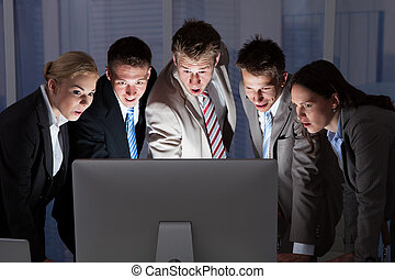 Surprised Business People Looking At Computer Monitor -...