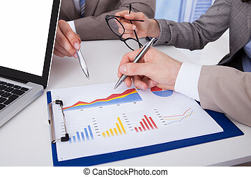 Business People Discussing Over Graph In Office - Midsection...