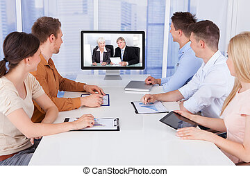 Business People Looking At Computer Monitors In Office
